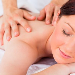 Woman smiling at Camera as she destresses & beats insomnia with Swedish massage & reflexology in bridal package