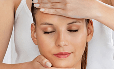 Woman with eyes closed facing camera as massage therapist gives her a pamper package swedish, indian head and reflexology