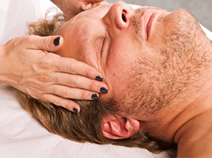 Man who needs to relax enjoying Reiki during a tranquility ritual