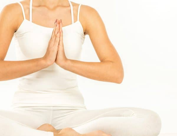 Woman dressed in white doing fertility yoga for infertility at Essential Feeling