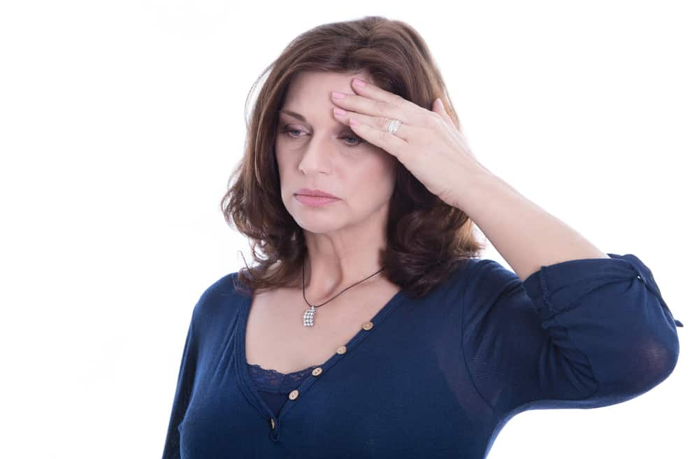 middle aged woman suffering with menopause holds forehead