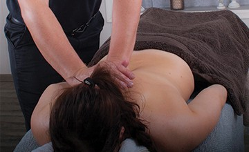 Woman lying on front covered with towel while Charlton, the therapist at Essential Feeling massages her shoulder