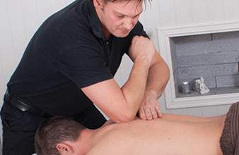 Man having deep tissue massage therapy with elbow in his shoulder at Essential Feeling for sports injury and rehabilitation